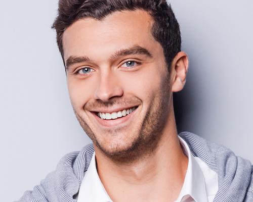 یک مرد خندان که دندان های مرتبی دارد